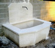 Old stone fountain of reconstituted limestone